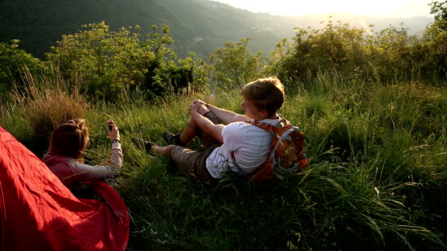 Young couple relax beside tent, take picture towards sunrise video