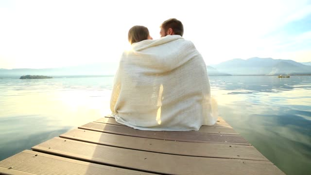 Young couple relaxes on lake pier, wrapped in blanket video