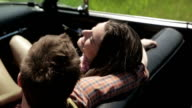 Young couple relaxing in convertible outdoors video
