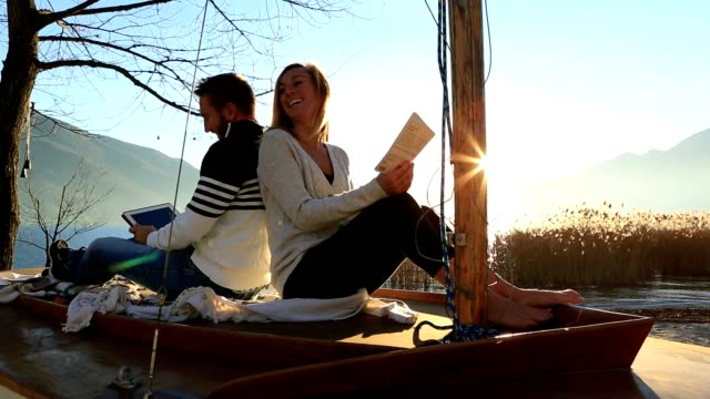 Young couple relaxing in nature, reading book and digital tablet video