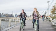 Young couple riding bicycles on promenade video