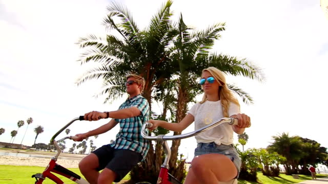 Young Couple Riding Bikes At Beach Slow Motion video
