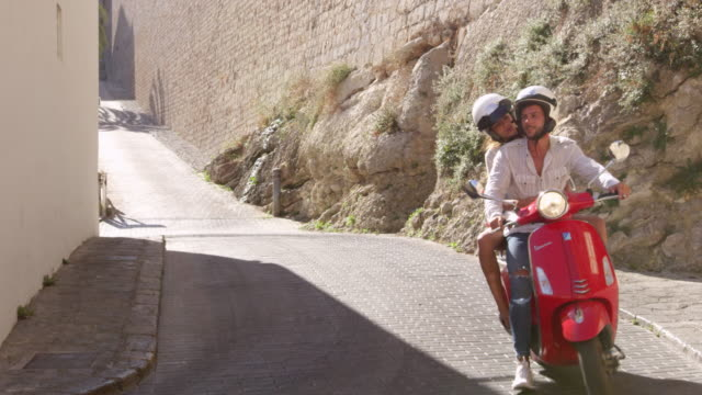 Young couple riding on a scooter, Ibiza, Spain, shot on R3D video