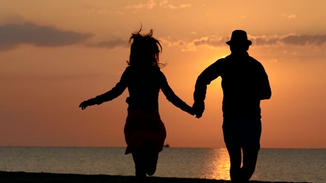 Young couple runing on the sunset - slowmotionn video