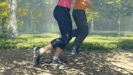 Young couple running in a sunny forest close up video
