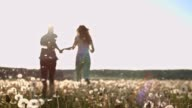 SLO MO Young couple running through dandelion seeds video