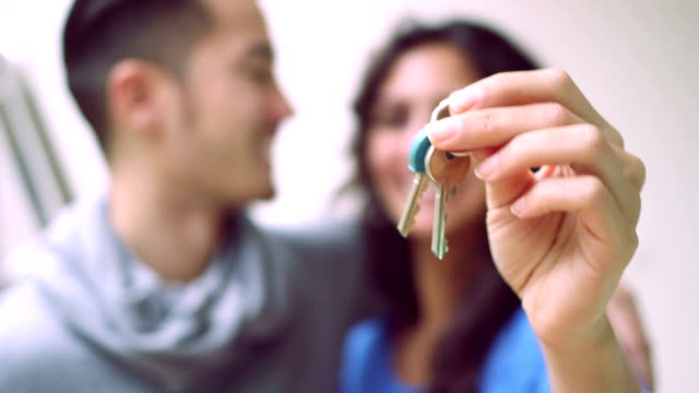 Young couple showing keys and kissing each other video