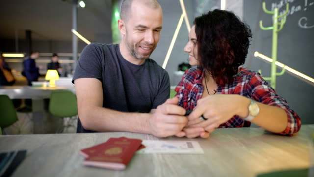 Young couple sitting at a table and looking at smartphone screen by clicking on it with their fingers. Man and woman reviewing their photos on the gadget while laughing and actively comment on them video