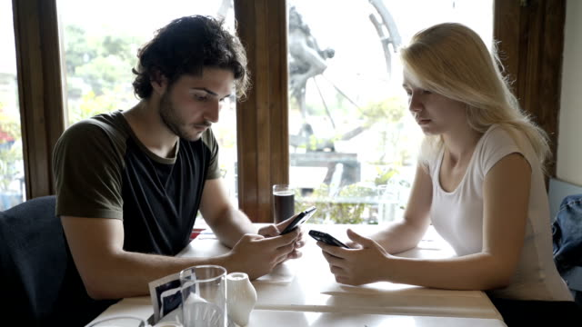Young couple sitting at cafe table and texting messages on smartphone exchanging upset looks video
