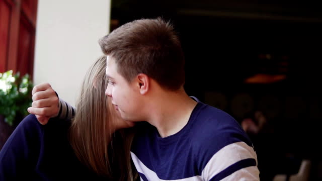 Young couple sitting at the table in cafe, embracing each other and talking Slowmotion. video