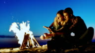 Young couple sitting by the fire in the evening, warm your hands by the fire video