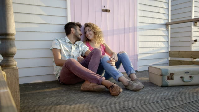 Young couple sitting hut video