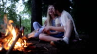 Young couple sitting in a forest fire. The guy kisses the girl. video