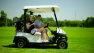 Young couple sitting in the cart at the course video