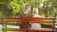 Young couple sitting on bench video