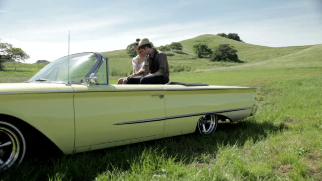 Young couple sitting on rear of vintage convertible car video
