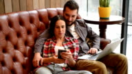 young couple sitting on sofa and using gadgets video