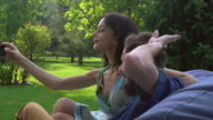 Young couple sitting on the ottoman in the park and makes selfie video