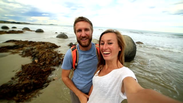 Young couple stand near Moeraki boulders and take selfie portrait video