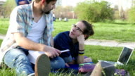 Young couple studying in the park and talking video