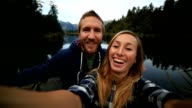 Young couple take a selfie portrait by the lake video