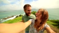 Young couple take a selfie portrait over grassy coastline hill video