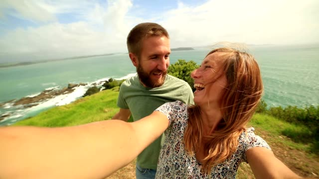 Young couple take a selfie portrait over grassy coastline hill video
