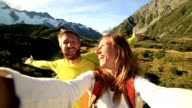 Young couple take self portrait on mountain background video