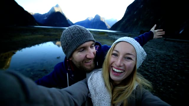 Young couple take selfie portrait in Milford sound, NZ video