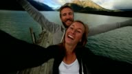 Young couple taking a selfie on a wooden jetty video