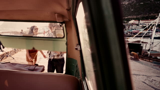Young couple taking a suitcase in their vintage van video