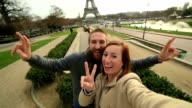 Young couple taking selfie at the Eiffel Tower, Paris video