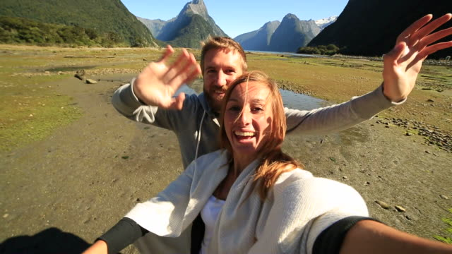 Young couple taking selfie portrait at Milford Sound video