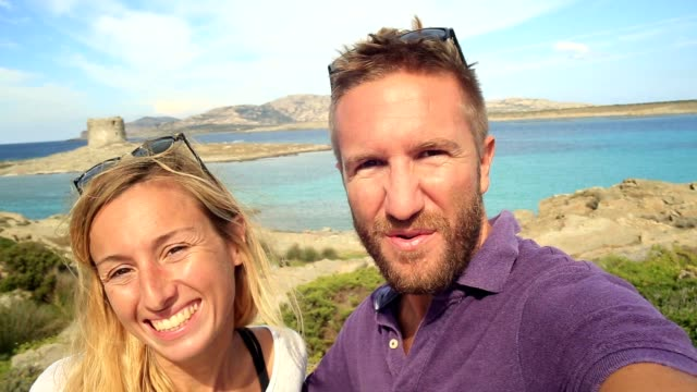 Young couple taking selfie portrait on vacations by the sea video