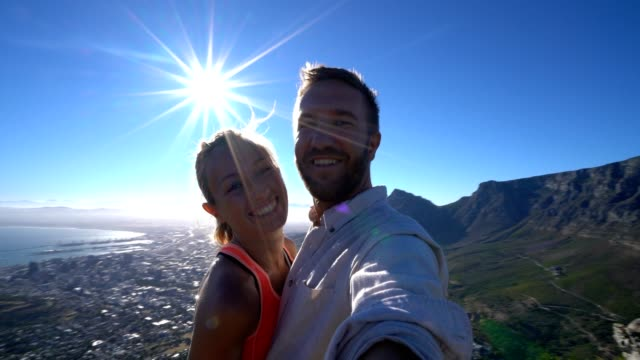 Young couple taking selfie with Cape Town cityscape at sunrise video