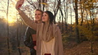 Young couple taking selfies in autumn forest video