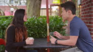 A young couple talking on a date at an outdoor cafe video