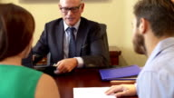 Young Couple Talking To Financial Advisor In Office video