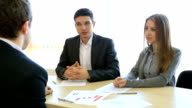Young couple talks to financial adviser video
