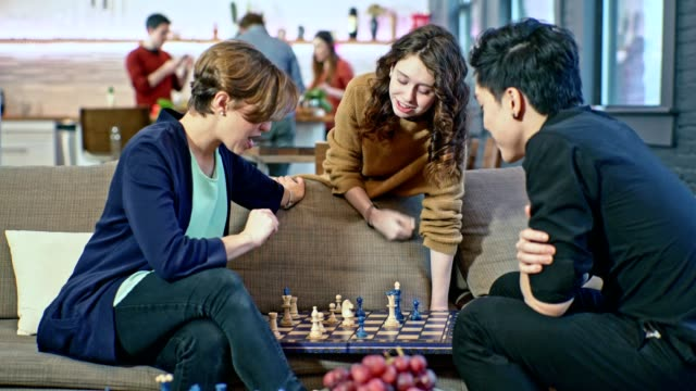 Young couple, the Caucasian girl and the Asian guy, playing chess game on the coach in the living room, when teenager girl, probably the younger sister, giving some advice about the game. Same time, group of people in the backdrop cooking in the kitchen. video