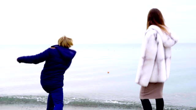 Young couple throwing rocks into the sea in the winter. Slow motion video