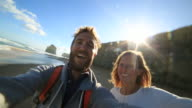 Young couple traveling take selfie on beach video