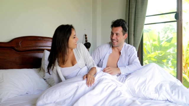 Young Couple Waking Up In Bed Stretching Arms, Beautiful Girl And Man In Bedroom Morning video