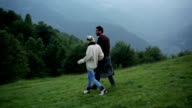 Young couple walk on mountain at sunset video HD video
