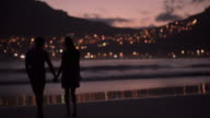Young couple walking and holding hands at the beach video