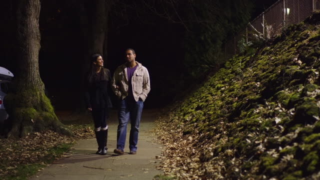 A young couple walking down a sidewalk at night video