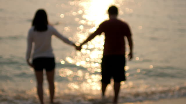 Young Couple Walking on Beach to the sea holding hands at sunset time ,Blurred motion ,relaxation concept video