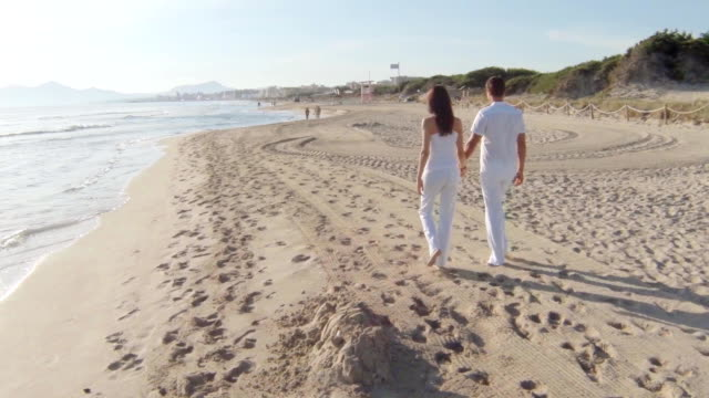 young couple walking on the beach video