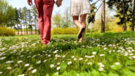 Young couple walking through park in springtime, low section video