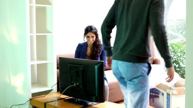 Young couple watching LCD television and talking video